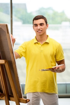 明るいスタジオで絵を描く若い男性アーティスト