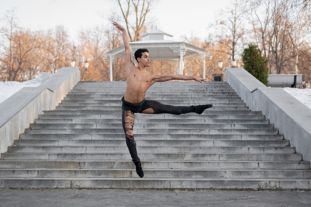 Young male artist performing on street ballet