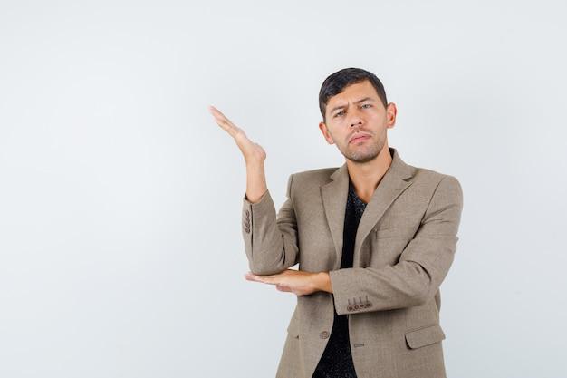 Молодой мужчина спрашивает что-то, указывая в сторону в серовато-коричневой куртке и нервно глядя, вид спереди.