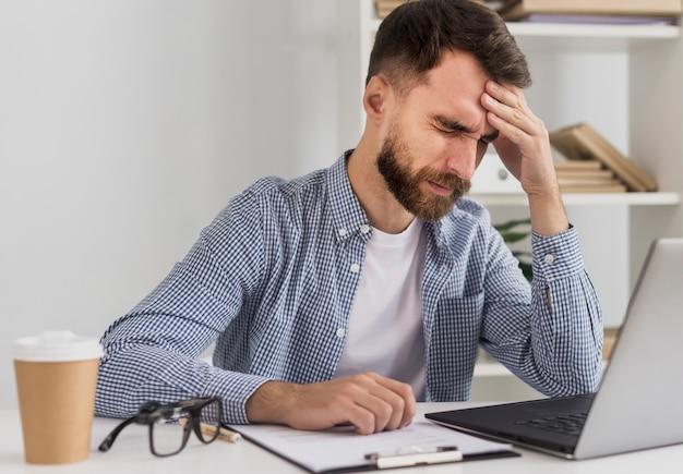 Молодой мужчина в офисе работает макет