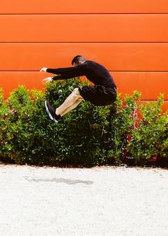 Giovane atleta maschio che fa un salto in lungo sulla sabbia