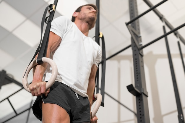 Young male athlete exercising with gymnastic rings in the gym