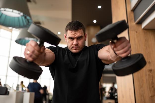 若い男性アスリートフィットネスクラブがダンベルを上げる上半身の筋肉群