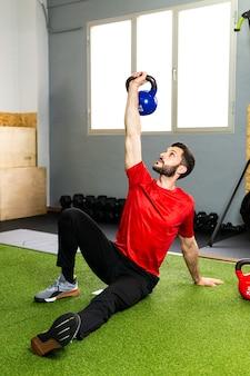 ジムでの重量挙げトレーニング中にコンクリートの床に重いケトルベルを握る若い男性アスリート
