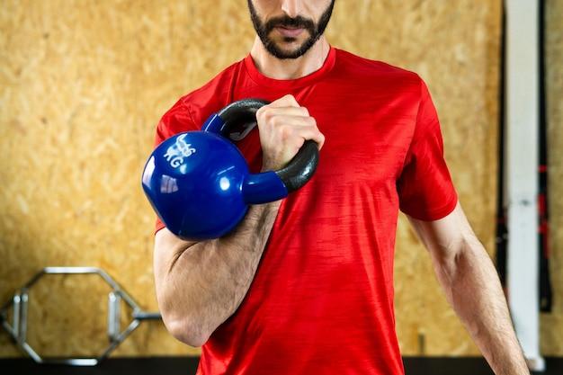 ジムでの重量挙げトレーニング中にコンクリートの床に重いケトルベルを握る若い男性アスリート Premium写真