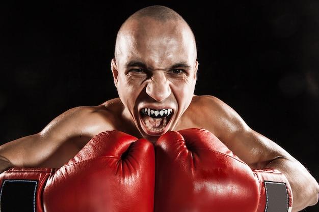 Il giovane atleta maschio kickboxing su un nero con kapa in bocca. furia di concetto nella lotta