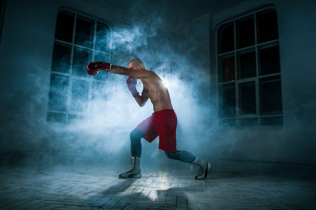 The young male athlete kickboxing on a of blue smoke