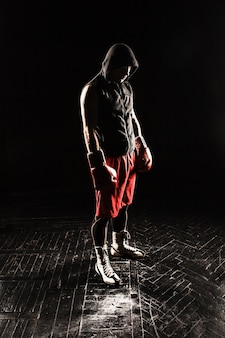The young male athlete kickboxing standing against black background