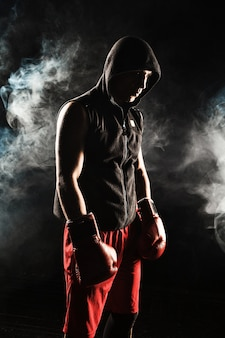 The young male athlete kickboxing standing on a background of blue smoke