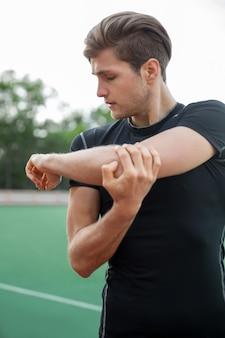 若い男性アスリートが屋外でストレッチ体操を行う
