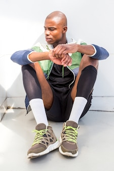 A young male athlete sitting on ground looking away
