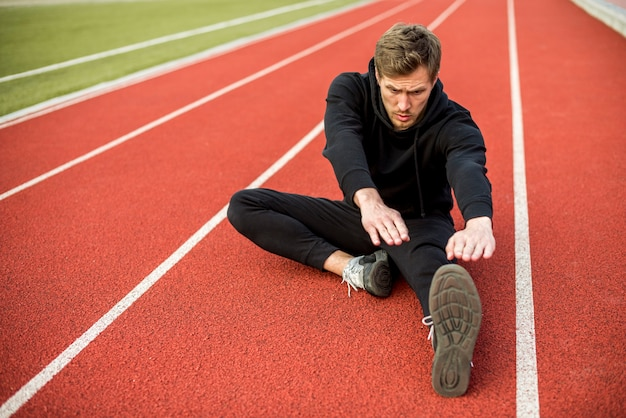 Young male athlete sitting on race track stretching his hand and legs
