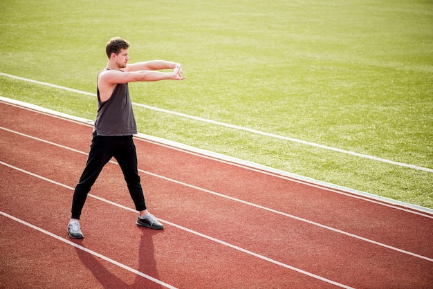 Young male athlete standing on race track stretching her hands