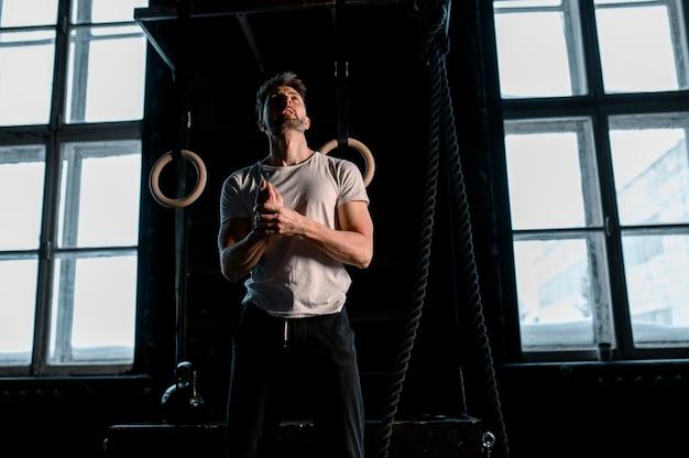 ジムで体操リングを持つ若い男性アスリートはリングに焦点を当てる高品質の写真