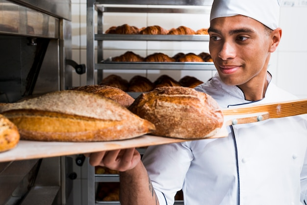 Young male baker taking out with wooden shovel freshly baked bread from the oven