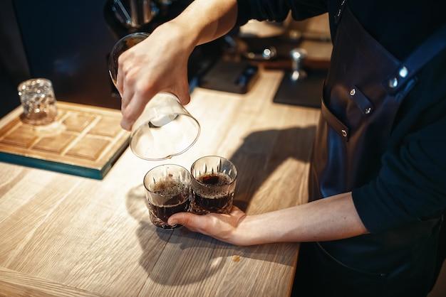Молодой мужчина-бариста делает свежий черный кофе
