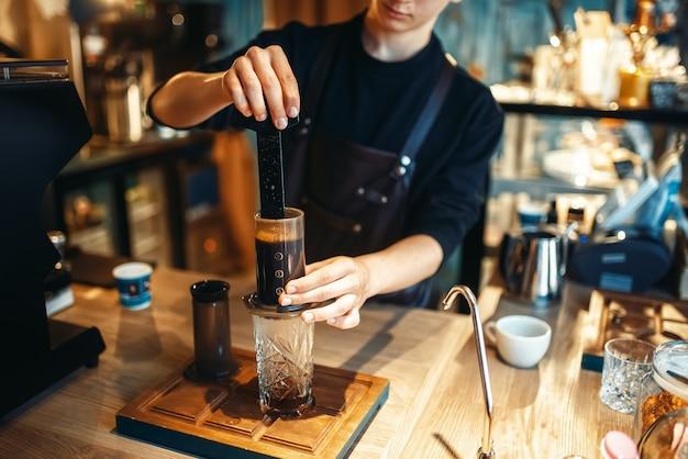 若い男性のバリスタがカフェで新鮮なエスプレッソを作る