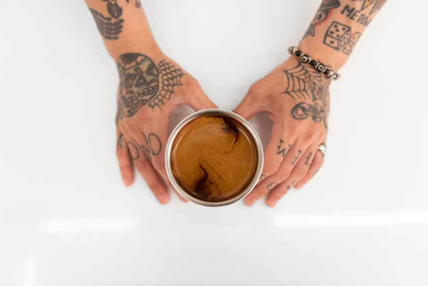 Young male barista with tattoos holding cup of freshly brewed coffee