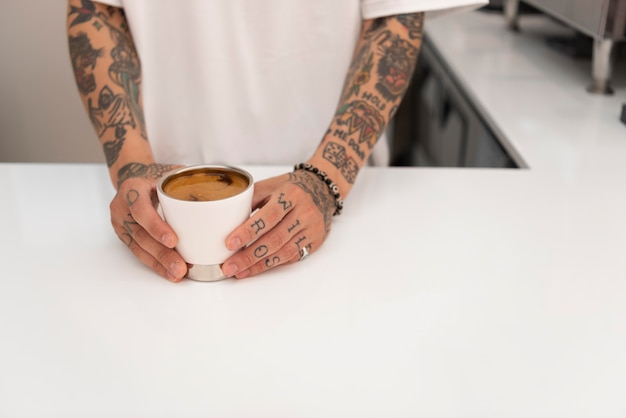 淹れたてのコーヒーのカップを保持している入れ墨を持つ若い男性のバリスタ