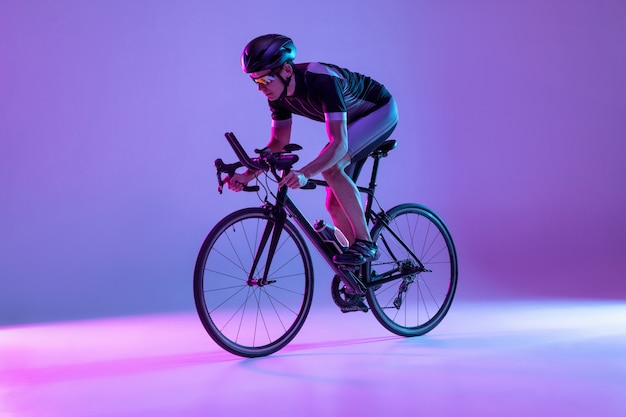 Young male bike rider on bicycle isolated on gradient wall in neon man training and practicing