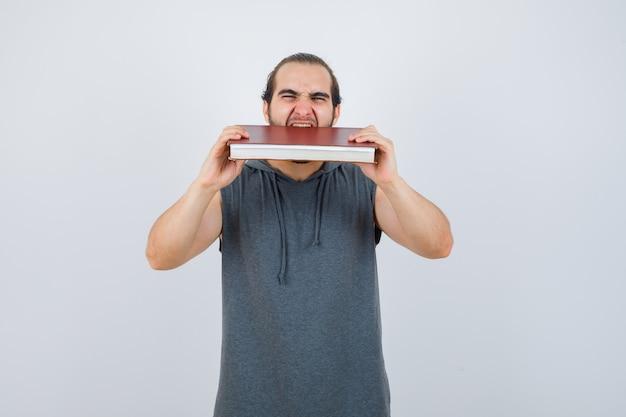 Молодой мужчина кусает книгу в толстовке без рукавов и выглядит голодным. передний план.