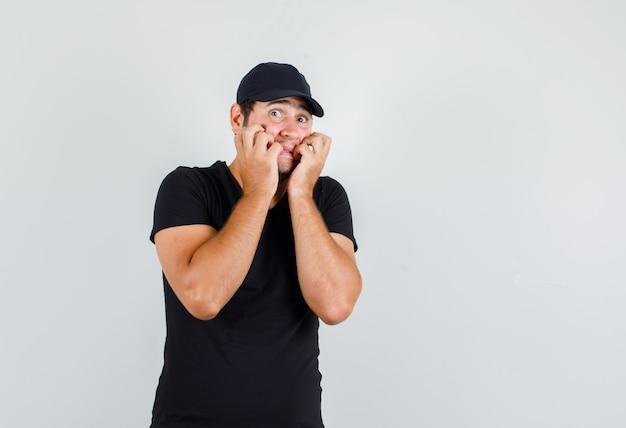 黒のtシャツで感情的に拳を噛む若い男性
