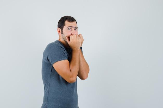 若い男性は灰色のtシャツで感情的に拳を噛み、怖がって見える