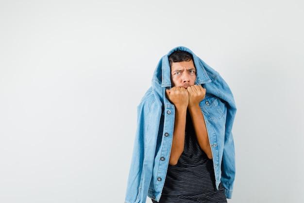 若い男性がtシャツのジャケットで感情的に拳を噛み、おびえているように見える