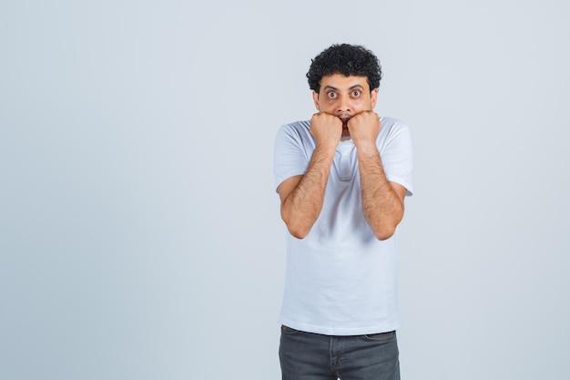 젊은 남성은 흰색 티셔츠, 바지를 입고 겁에 질린 표정으로 감정적으로 주먹을 물어뜯습니다. 전면보기.
