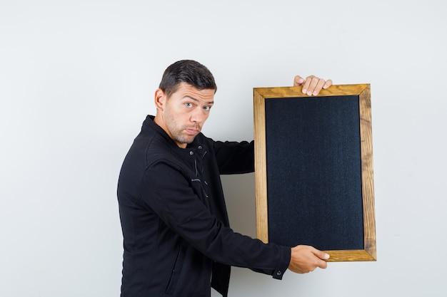 Giovane maschio in giacca nera che tiene lavagna e che sembra serio, vista frontale.