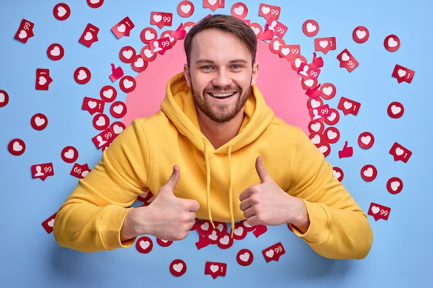 Young male blogger is happy to get a lot of likes and views, stand among heart signs buttons