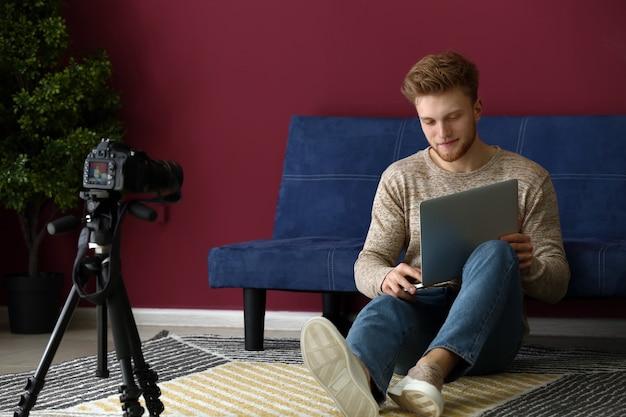 Молодой мужчина-блоггер, записывающий видео дома