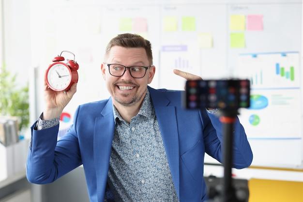 젊은 남성 블로거는 카메라 시간 제어 훈련 및 시간에 빨간색 알람 시계로 비디오를 촬영합니다