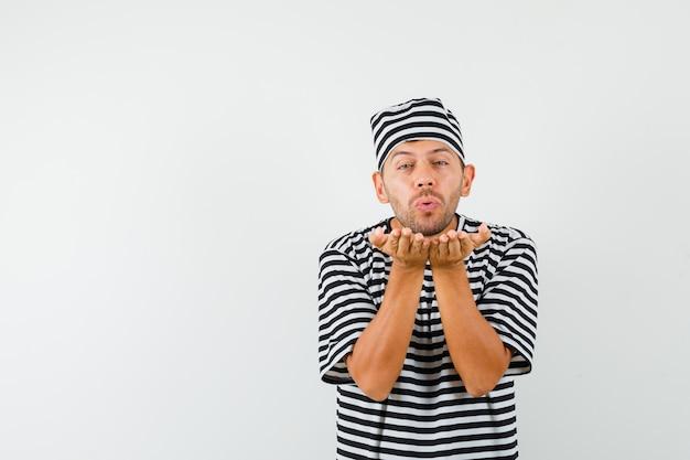 Giovane maschio che soffia aria bacio con labbra imbronciate in cappello t-shirt a righe
