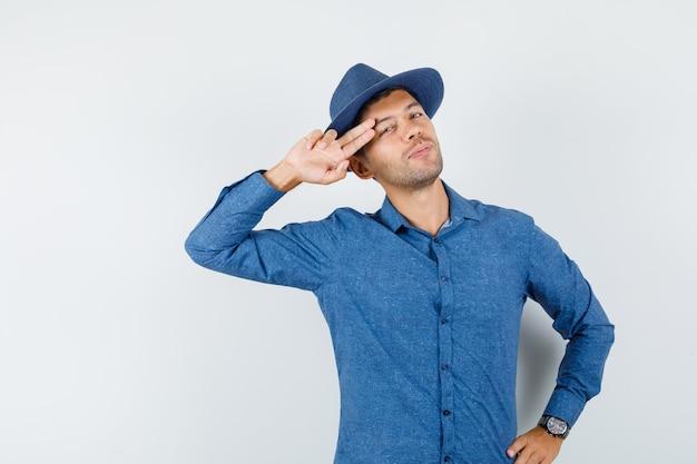 Giovane maschio in camicia blu, cappello che tiene due dita vicino alle tempie e sembra fresco, vista frontale.