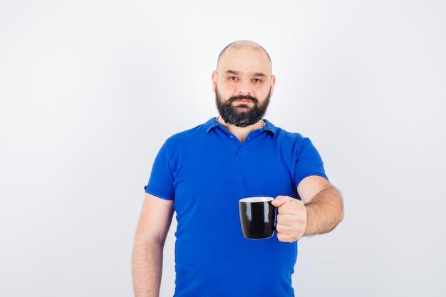 Giovane maschio in camicia blu che mostra una tazza nera alla telecamera e sembra felice, vista frontale.