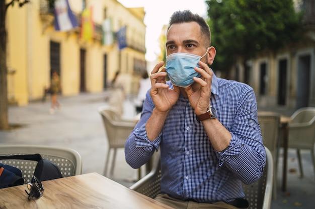 Giovane maschio in una camicia blu che indossa una maschera facciale medica seduto in un caffè all'aperto - concetto covid-19