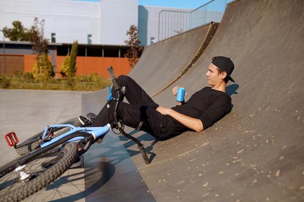 Молодой мужчина bmx байкер отдыхает на рампе, подросток на тренировке в скейтпарке. экстремальный велосипедный спорт, опасные велотренировки, риск-стрит, езда на велосипеде в летнем парке