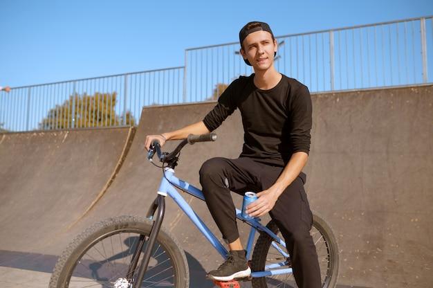Молодой мужчина bmx байкер отдыхает на рампе, подросток на тренировке в скейтпарке. экстремальный велосипедный спорт, опасные велотренировки, рискованная уличная езда