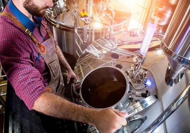 Молодой пивовар в кожаном фартуке наблюдает за процессом брожения пива на современном пивоваренном заводе ...