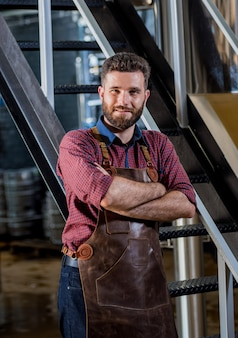 Young male brewer in leather apron at modern brewery factory