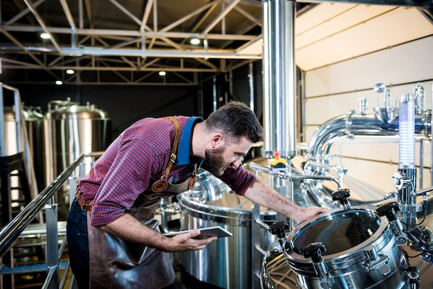 Young male brewer in leather apron supervising the process of beer fermentation at modern brewery fa...