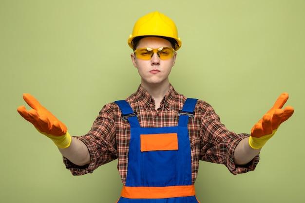 올리브 녹색 벽에 격리된 안경을 쓴 유니폼과 장갑을 끼고 있는 젊은 남성 건축업자