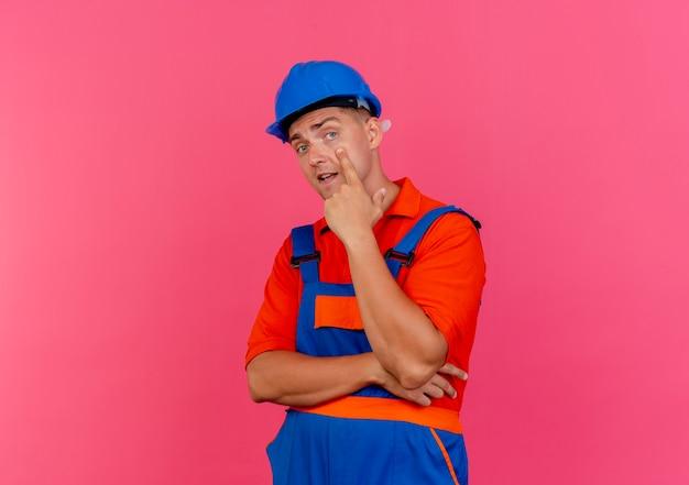 눈에 손가락을 넣어 유니폼과 안전 헬멧을 착용하는 젊은 남성 작성기