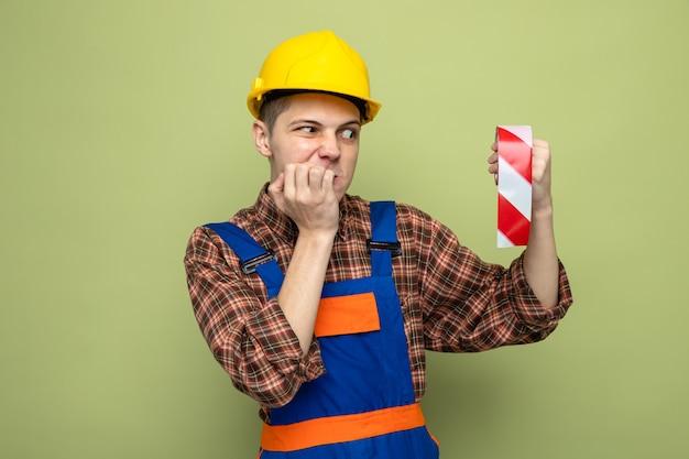올리브 녹색 벽에 격리된 덕트 테이프를 보고 제복을 입은 젊은 남성 건축업자