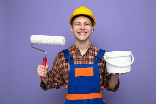 Giovane costruttore maschio che indossa un secchio di tenuta uniforme con spazzola a rullo isolato su parete viola
