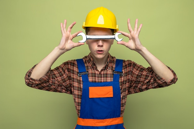 Young male builder wearing uniform holding and covered face with open-end wrench