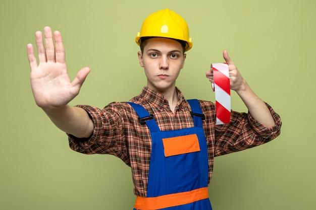 オリーブグリーンの壁に分離された均一な保持ダクトテープを身に着けている若い男性ビルダー