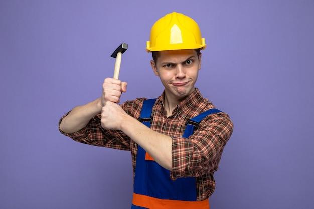 紫色の壁に分離された均一な保持ハンマーを身に着けている若い男性ビルダー