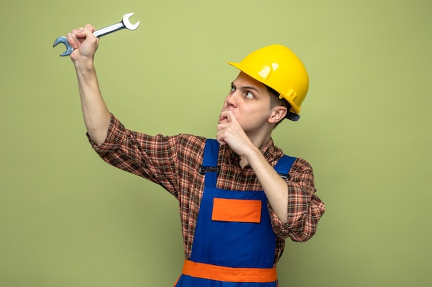 Young male builder wearing uniform holding and looking at open-end wrench isolated on olive green wall